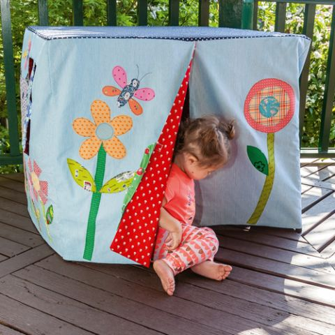 Styled shot of cubby house with little girl on verandah