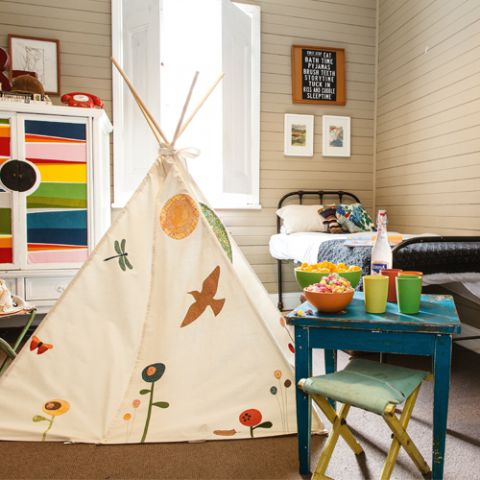 Styled shot of child's room with teepee featuring trees, flowers and birds