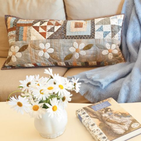 Styled shot of appliqué flower and patchwork cushion on couch