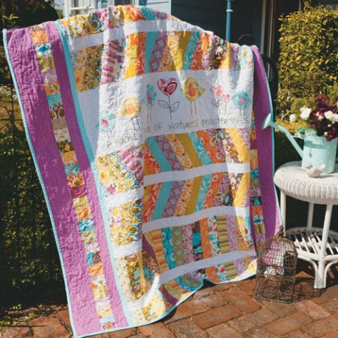 Styled shot of appliqué and embroidered bird quilt draped over fence