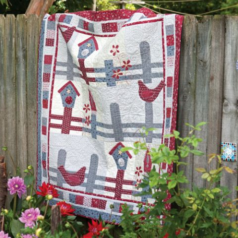 Styled shot of red and blue quilt with bird on fence and bird house draped over fence in garden outside