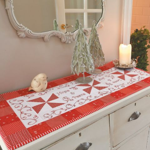 Styled shot of red and white embroidered Christmas tablerunner on side table