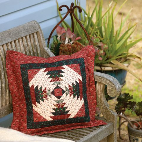 Styled shot of red patterned patchwork cushion on rustic bench seat
