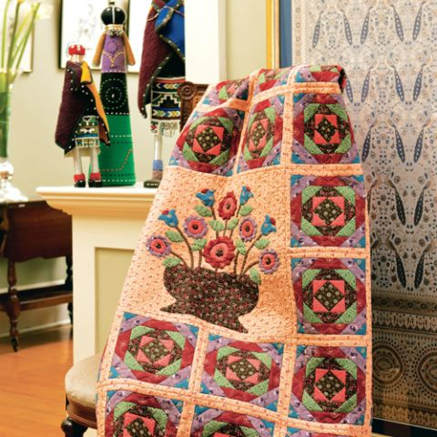 Styled shot of quilt draped over chair in living room with flower patchwork in the centre and  geometric square pattern