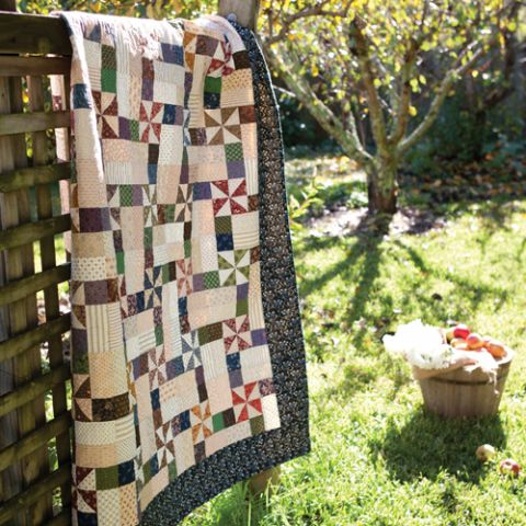 Styled shot of geometric pinwheel quilt draped on fence outdoors