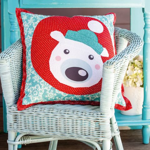 Styled shot of appliqué and foundation pieced christmas polar bear cushion on chair