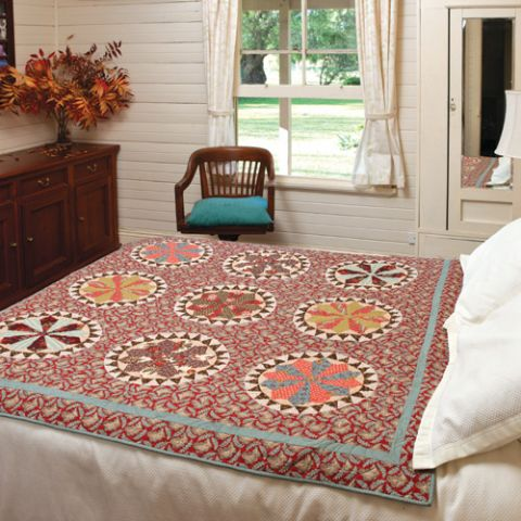 Styled shot of hand-pieced circle star quilt on bed