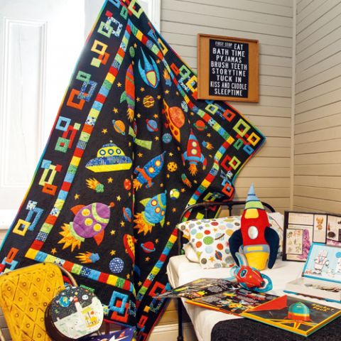 Styled shot of child's bedroom with rocketship quilt