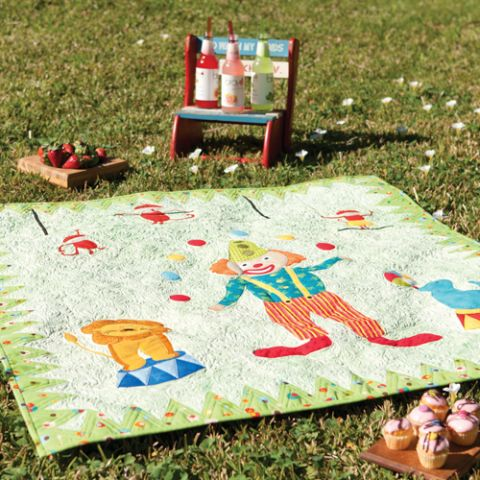 Styled shot of circus themed quilt with clown juggling lying on the grass