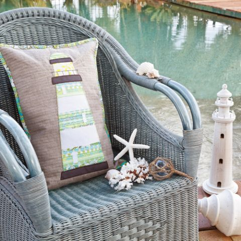 Styled shot of tall lighthouse cushion on wicker chair outside by the pool