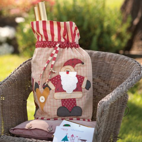 Styled shot of appliqué heart and santa bag outside on chair