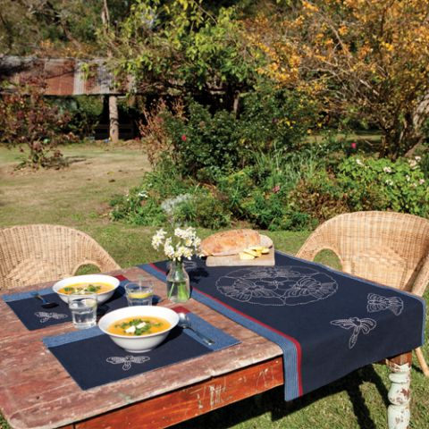 Styled shot of dragonfly and butterfly tablerunner and matching mats on a table set up in the garden