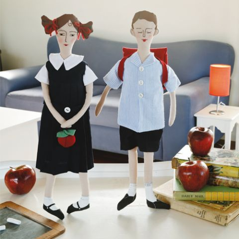 Styled shot of school boy and girl in uniform with backpack and apple
