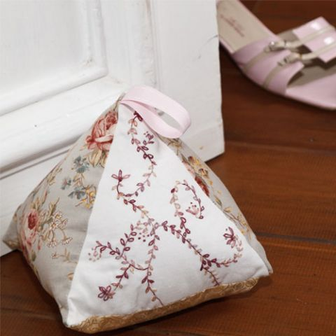 styled shot of pink embroidered doorstop