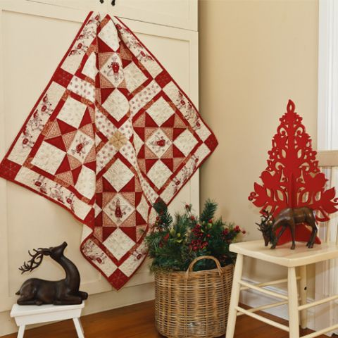 Styled shot of appliqué and embroiodered angel christmas quilt hanging up