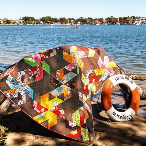 Styled shot of large pinwheel patchwork quilt by the water