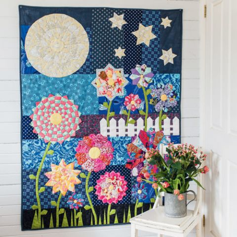Styled shot of night garden appliqué flower quilt hanging up
