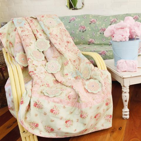 Styled shot of appliqué flower and patchwork pretty quilt draped over chair