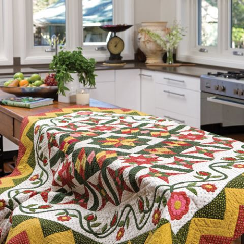 Styled shot of patchwork and appliqué quilt on table