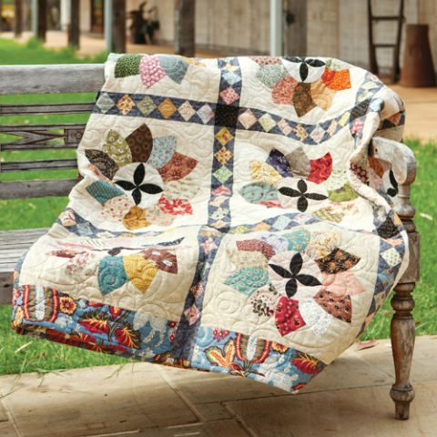 Styled shot of sunflower patterned patchwork quilt draped on bench in rustic scenery