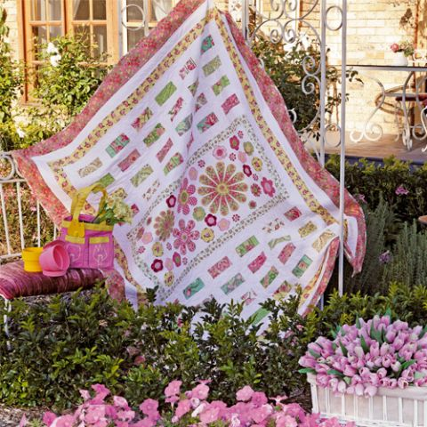 Styled shot of appliqué flower and patchwork quilt hanging up in garden