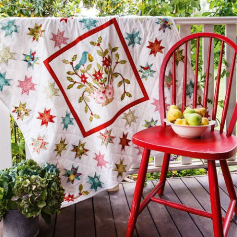 Styled shot of appliqué and patchwork partridge quilt draped over railing