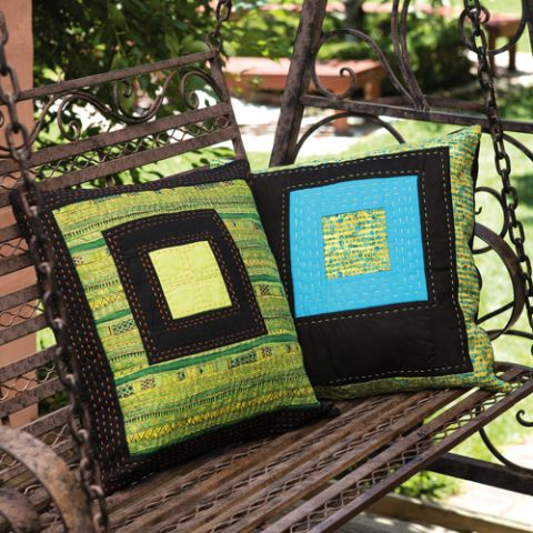 Styled shot of square patterned cushions sitting on swinging chair outside