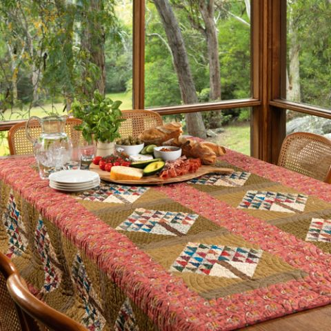 Styled shot of patchwork quilt on table with repeated geometric tree pattern