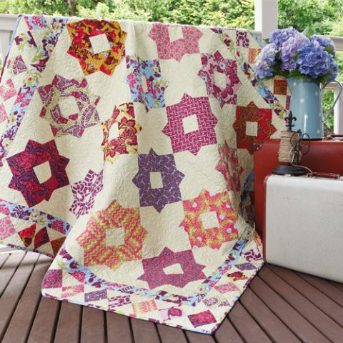 Styled shot of patchwork diamond quilt draped over railing