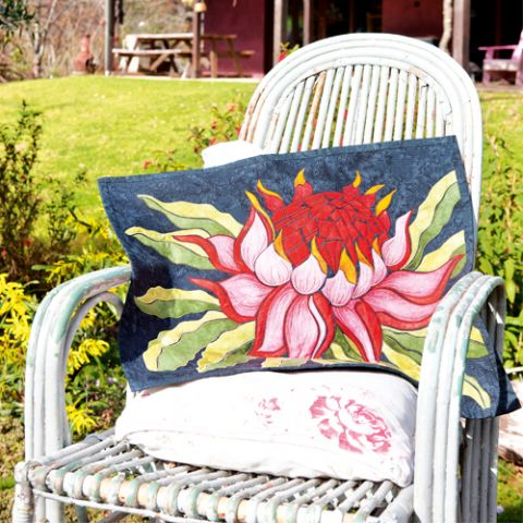 Styled shot of waratah flower wallhanging lying across rustic chair outdoors