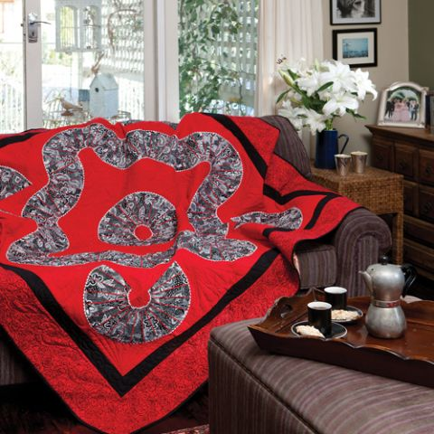 Style shot of red and black quilt draped on lounge with organic shapes